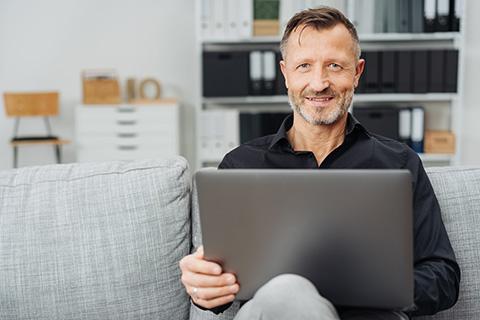 Mann sitzt auf dem Sofa mit Laptop auf dem Schoß.