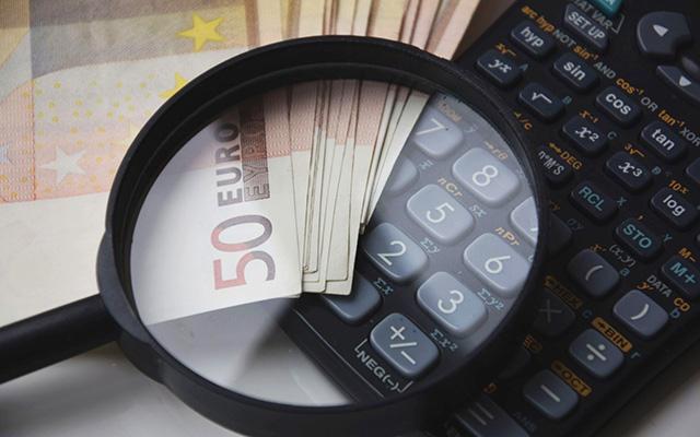 Geldscheine und ein Taschenrechner liegen unter einer Lupe auf dem Tisch.