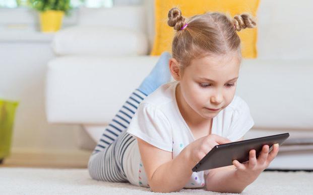 Kleines Mädchen liegt auf dem Bauch mit einem Tablet in den Händen