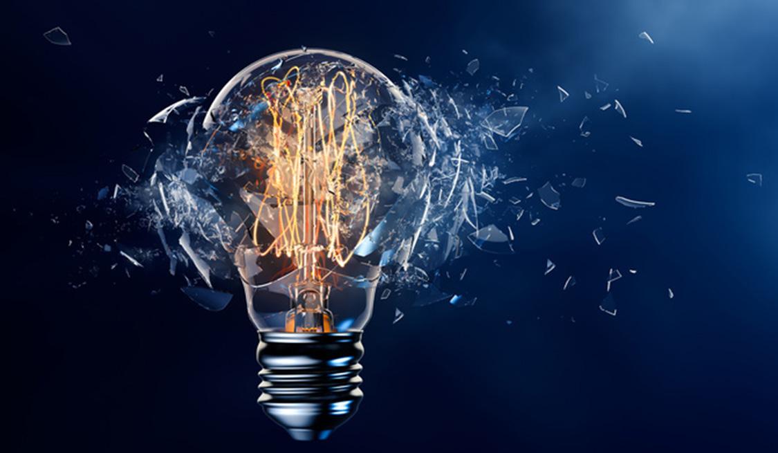 Eine leuchtende Glühbirne platzt und Scherben fliegen durch die Luft