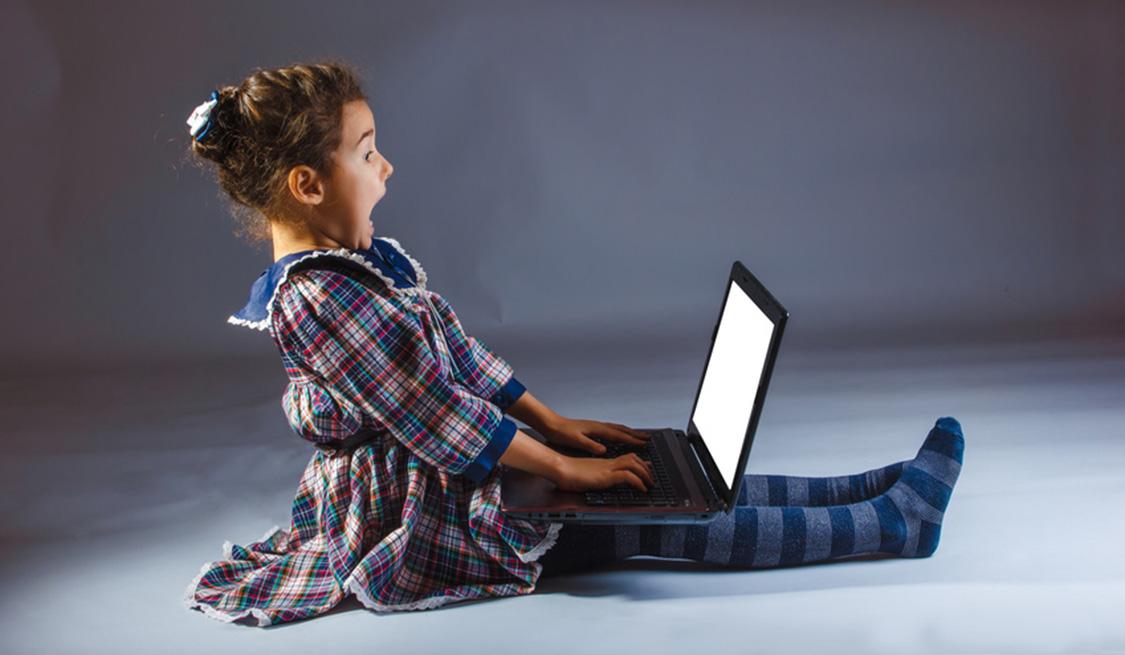 Mädchen schaut erschrocken auf den Laptop auf ihrem Schoß.