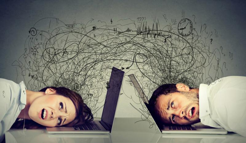 Mann und Frau sitzen sich gegenüber und haben ihren Kopf auf der Tastatur ihrer Laptops. Über ihren Köpfen verwirrte Gedanken.