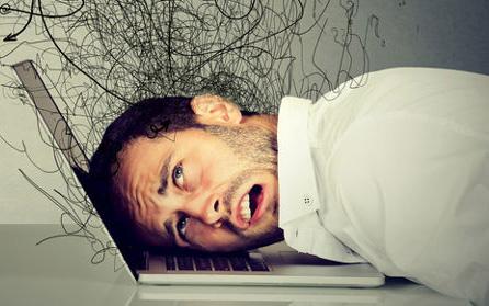 Mann legt Kopf auf die Tastatur seines Laptops. Über ihm schwirren verwirrte Gedanken.