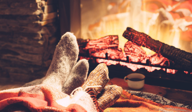 Die Füße zweier Personen sind eingekuschelt in dicken Socken und mit einer Wolldecke vor dem Kamin.