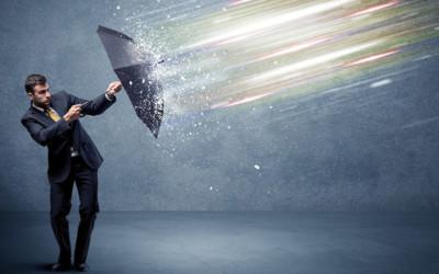 Mann im Anzug schützt sich mit einem Regenschirm vor einprasselndem Hagel