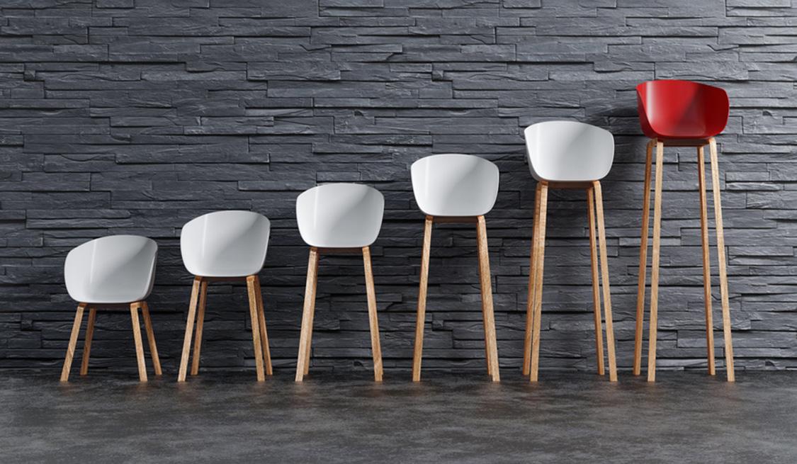 Fünf weiße und ein roter Stuhl stehen nebeneinander mit immer länger werdenden Stuhlbeinen vor einer grauen Mauer