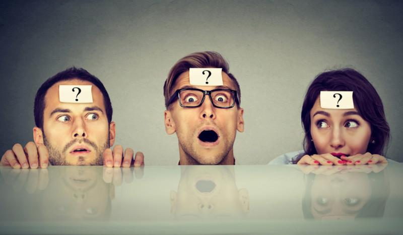 Drei Personen schauen hinter einer Tischplatte hervor mit einem Zettel an Stirn, auf dem eine Fragezeichen zu sehen ist.