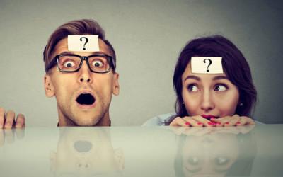 Ein Mann und eine Frau schauen hinter einem Tisch hervor. Auf ihrer Stirn klebt jeweils ein Zettel mit einem Fragezeichen
