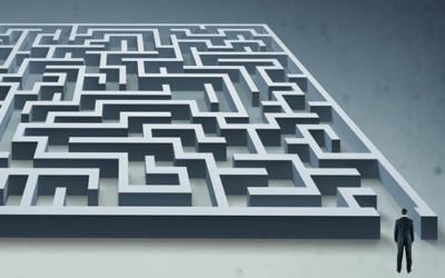 Mann im Anzug steht vor einem Labyrinth