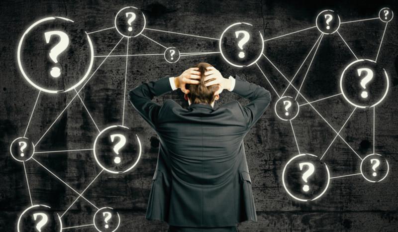 Mann schlägt die Hände über den Kopf zusammen und steht vor einem Rätsel