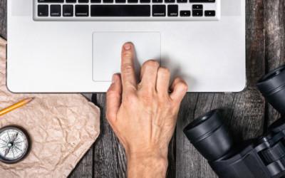 Mann hält einen Finger auf das Mousepad seines Laptops. Daneben liegen Kompass und Fernglas.