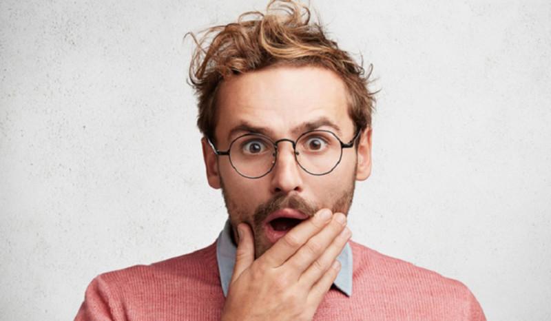 Mann hält sich erschrocken die Hand an den geöffneten Mund.