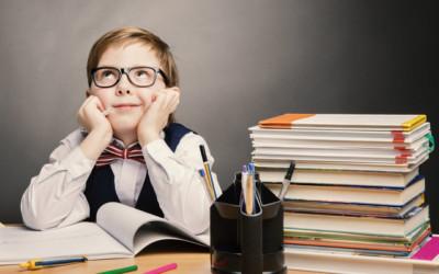 Kleiner Junge mit Brille, Hemd, Weste und Fliege sitzt am Schreibtisch. Den Kopf in die Hände gestützt und nach oben schauend. Neben ihm ein Stapel Bücher und Büro-Utensilien.