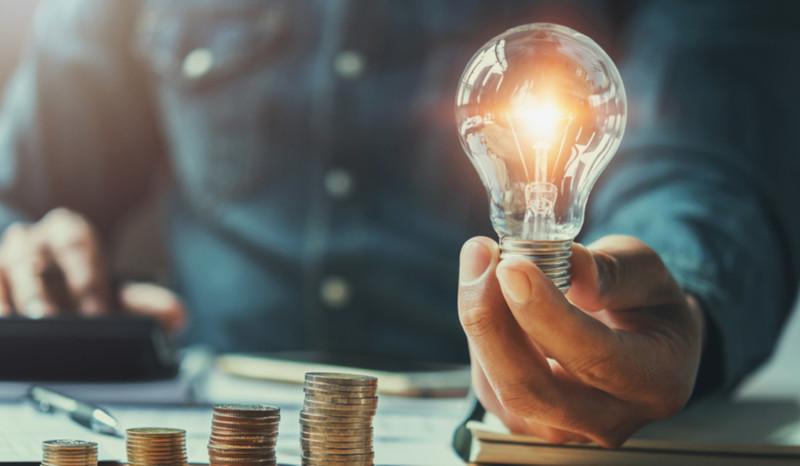 Mann hält leuchtende Glühlampe in der Hand. Daneben ein paar Stapel Geldmünzen