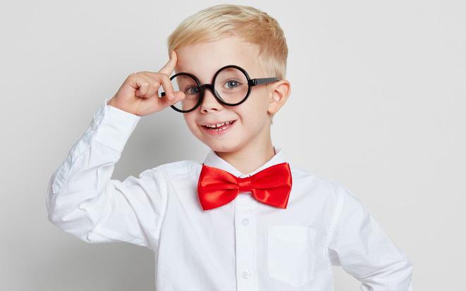 Kleiner Junge mit Brille, Hemd und roter Fliege hat eine zündende Idee.