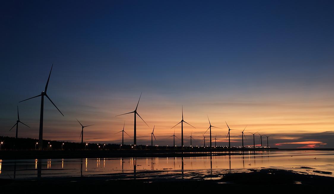 Blick vom Wasser: eine Vielzahl an Windrädern bei abendrotem Himmel.
