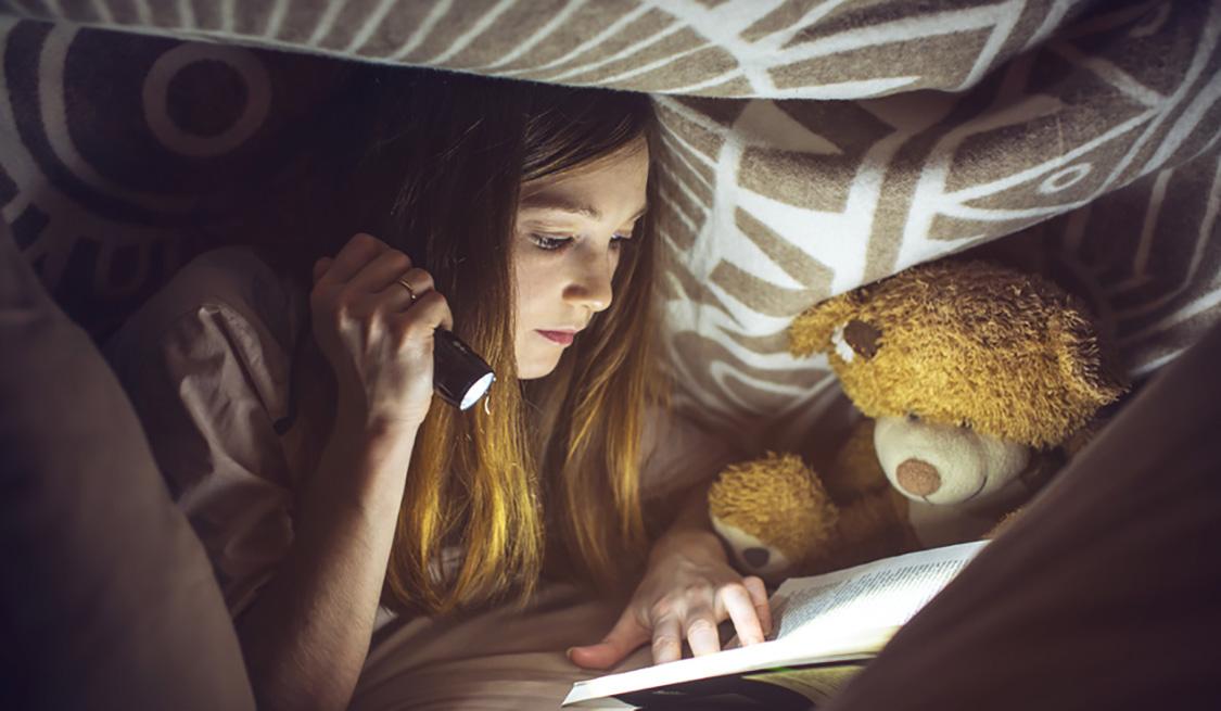 Mädchen Liegt mit Taschenlampe und Buch unter der Bettdecke.