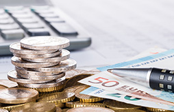 Geldscheine und gestapelte Münzen liegen auf einem Schreibtisch. Daneben ein Kugelschreiber und eine Computertastatur.