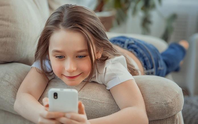 Mädchen liegt auf dem Sofa mit einem Smartphone in den Händen.