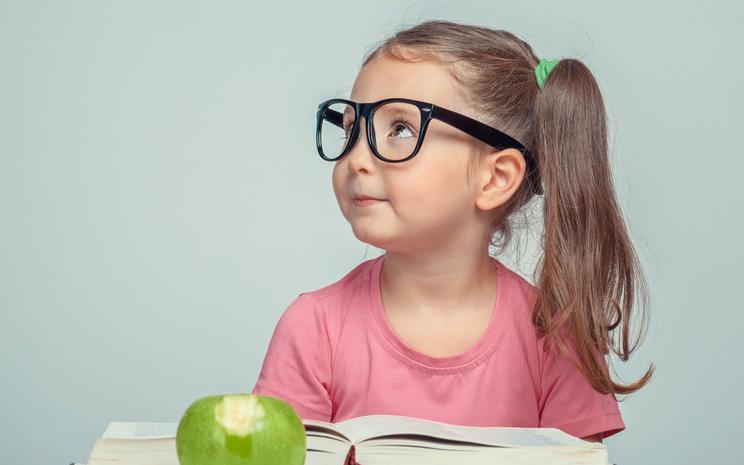 Kleines Mädchen mit Brille schaut nach links. Vor ihr ein aufgeschlagenes Buch und ein angebissener Apfel.