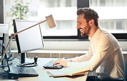 Mann sitzt am Schreibtisch mit Computer und Büro-Utensilien.