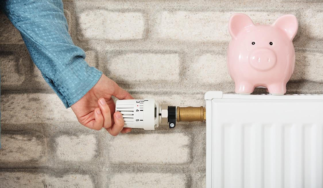 Eine Person hat die Hand am Temperaturregler einer Gasheizung. Auf der Heizung steht ein rosa Sparschwein.