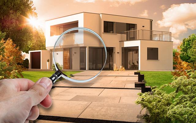 Modernes Wohnhaus mit Garten. Eine Hand hält eine Lupe vor das Haus.