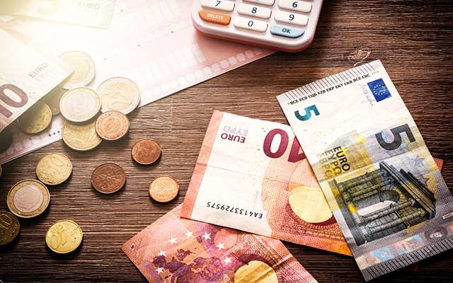 Geldscheine, Münzen und ein Taschenrechner liegen auf dem Tisch.