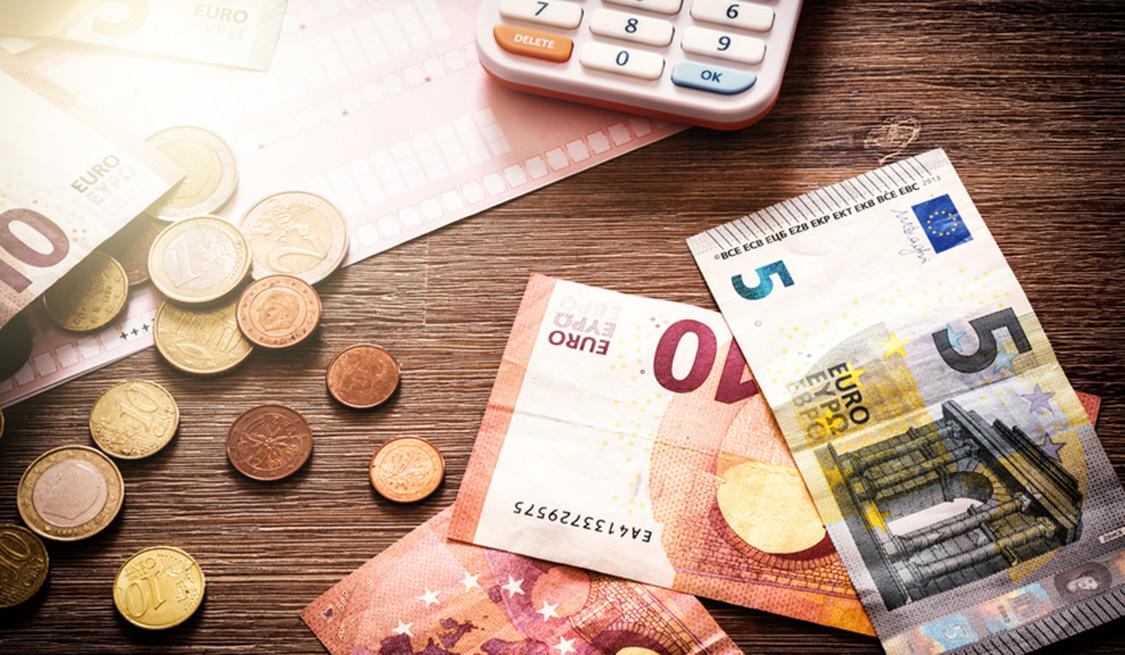 Geldscheine und Münzen liegen auf einem Holztisch. Im Hintergrund ein Taschenrechner.