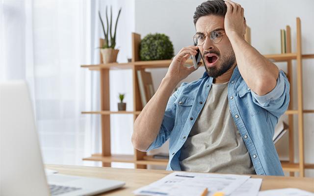 Mann sitzt am Tisch vor dem Laptop und seinem Unterlagen. Er telefoniert aufgeregt.