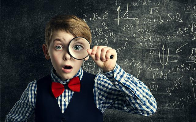 Kleiner Junge mit kariertem Hemd, Weste und roter Fliege hält sich eine Lupe vor das linke Auge. Hinter ihm eine Tafel mit mathematischen Formeln angeschrieben.