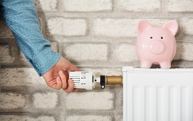 Eine Person hat die Hand am Temperaturregler einer Heizung. Auf der Heizung steht ein rosa Sparschwein.