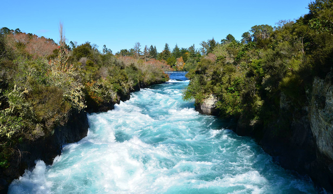 Wasserkraft   ErEin reißender Fluss, links und rechts Steinklippen und Grüngewächse.