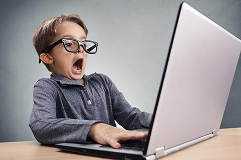 Kleiner Junge mit Brille sitzt erschrocken vor dem Laptop.