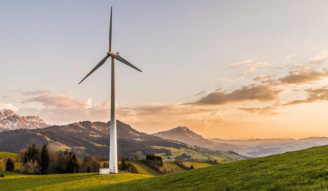Windmühle auf einer Wiesenlandschaft. Im Hintergrund ein Gebirge und abendroter Himmel