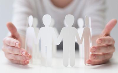 Eine Reihe Papiermännchen zwischen zwei Händen einer Person