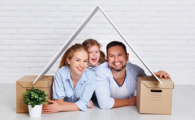 Mann, Frau und Kind liegen auf dem Bauch zwischen zwei Kartons mit einem Dach über ihren Köpfen.