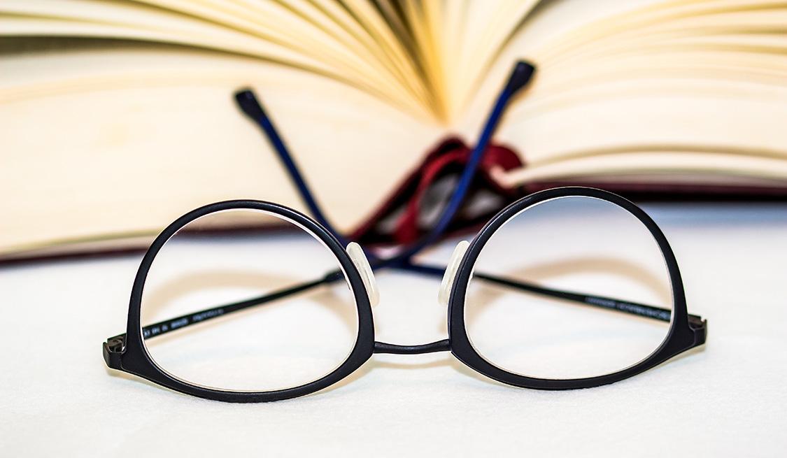 Brille liegt auf dem Kopf vor einem aufgeschlagenen Buch