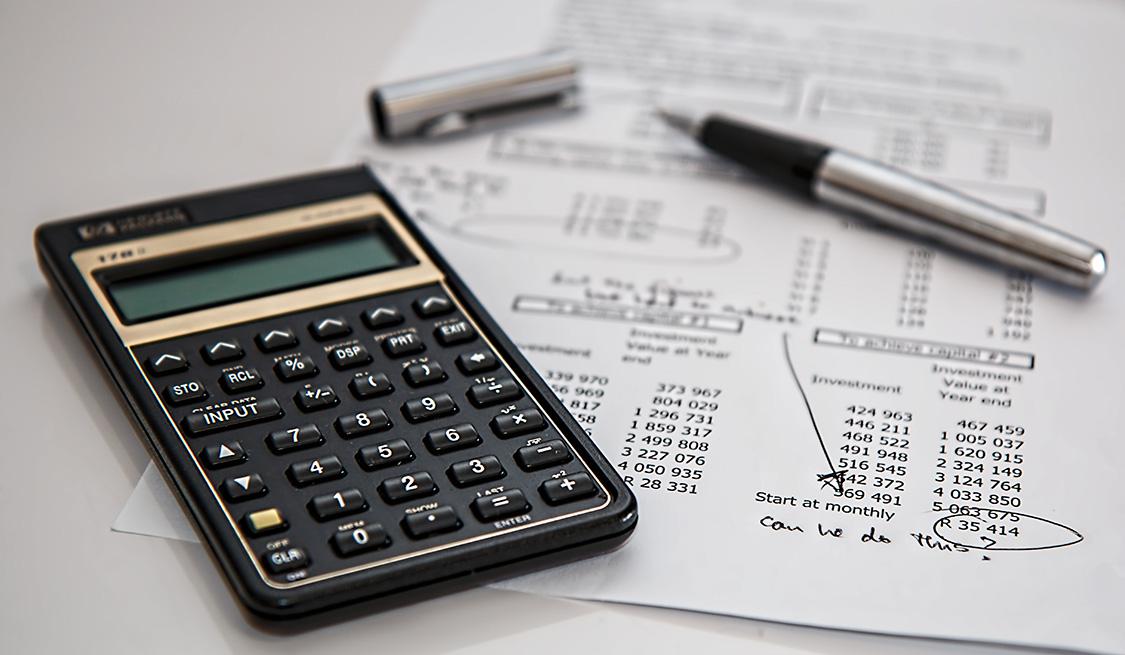 Stromrechnung, Taschenrechner und Kugelschreiber liegen auf dem Tisch.