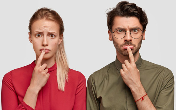 Mann und Frau stehen nebeneinander und schauen fragend.