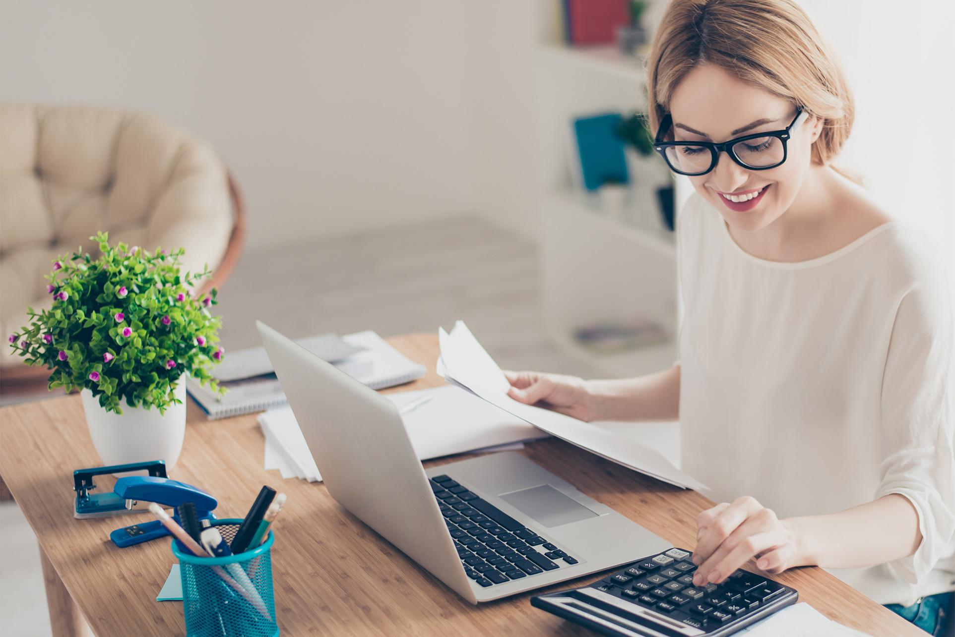 Frau sitzt am Tisch und bedient den Taschenrechner. Vor ihr steht der aufgeklappte Laptop und Unterlagen liegen bereit.