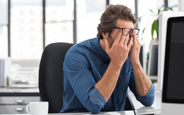Verzweifelter Mann sitzt am Schreibtisch und schlägt die Hände vor dem Gesicht zusammen