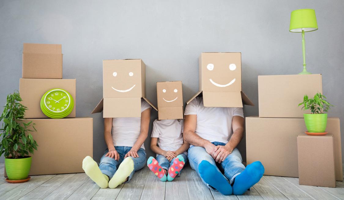 Eltern sitzen mit Kind zwischen Umzugskartons. Auf ihren Köpfen haben sie jeweils einen Karton übergestülpt mit einem Gesicht aufgemalt