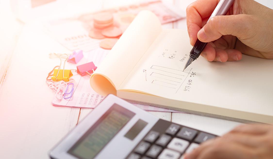 Eine Person berechnet die Stromkosten mit Notizblock und Taschenrechner. Im Hintergrund Büroutensilien und Bargeld.