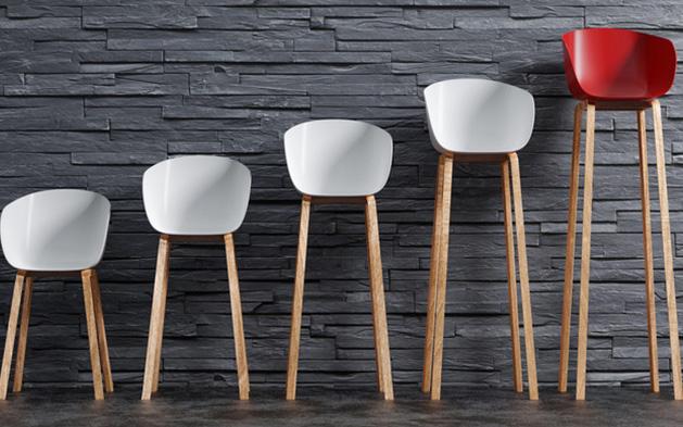 Vier weiße und ein roter Stuhl stehen nebeneinander mit immer länger werdenden Stuhlbeinen vor einer grauen Mauer