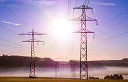Zwei Strommäste mit blauem Himmel und Sonnenschein im Hintergrund