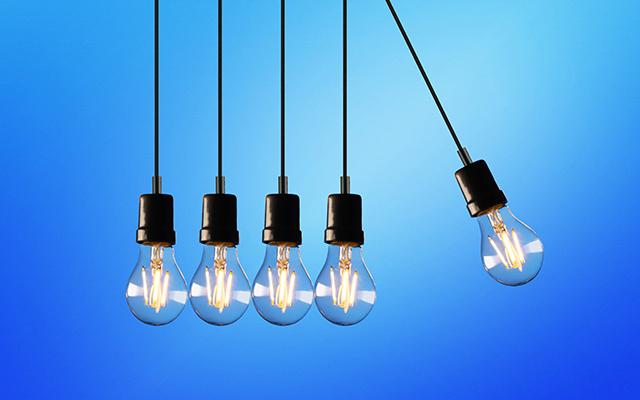 Fünf Glühlampen hängen von der Decke vor einem blauen Hintergrund. Die Lampe ganz rechts schwingt nach außen.