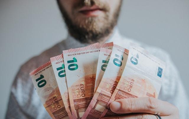 Mann mit Bart hält mehrere Zehn-Euro-Scheine in der Hand