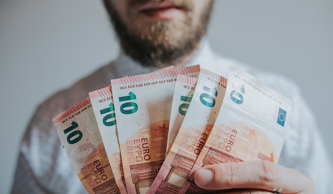Bärtiger Mann hält mehrere Zehn-Euro-Scheine in der Hand