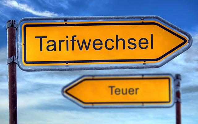 Zwei Schilder zeigen in entgegengesetzte Richtung mit den Aufschriften Tarifwechsel und Teuer.